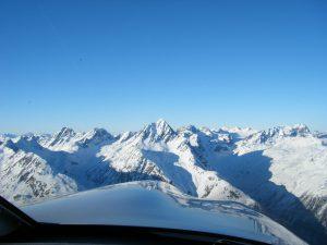Blick aus dem Cockpit einer Piper Archer III auf die verschneiten Schweizer Berge während der Ausbildung zum Privatpiloten.