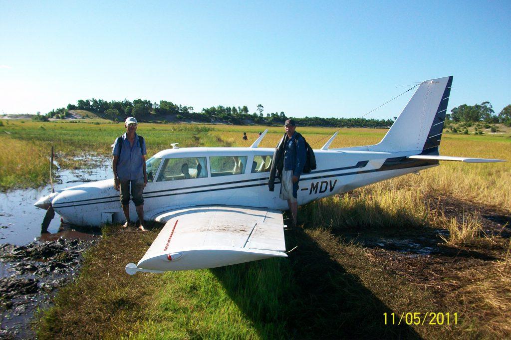 Kleinflugzeug nach einer Bruchlandung mit davor posierenden Piloten. Beispielbild, welches man am Recurrent Language Proficiency Check beschreiben müsste.