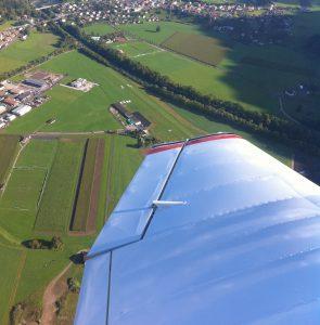Robin DR40 über dem Flugplatz Gruyère. Blick über den linken Flügel auf die Graspiste.