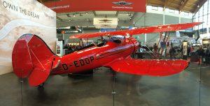 Eine rote WACO YMF-7, ein dreiplätziger Doppeldecker, ausgestellt an der Aero Friedrichshafen 2016.